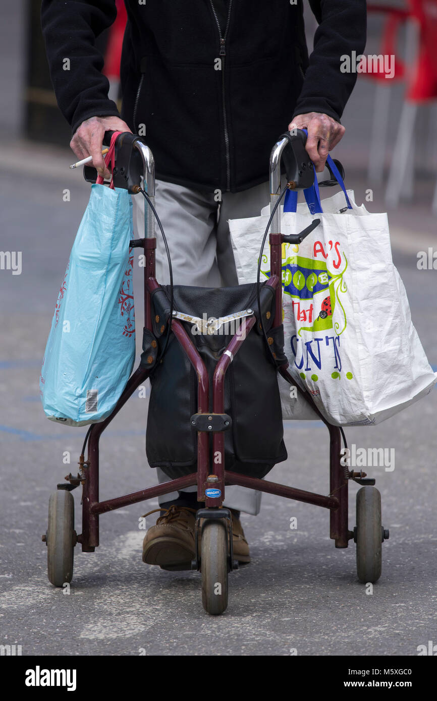 Un viejo pensionista utilizando un bastidor de soporte mientras ...
