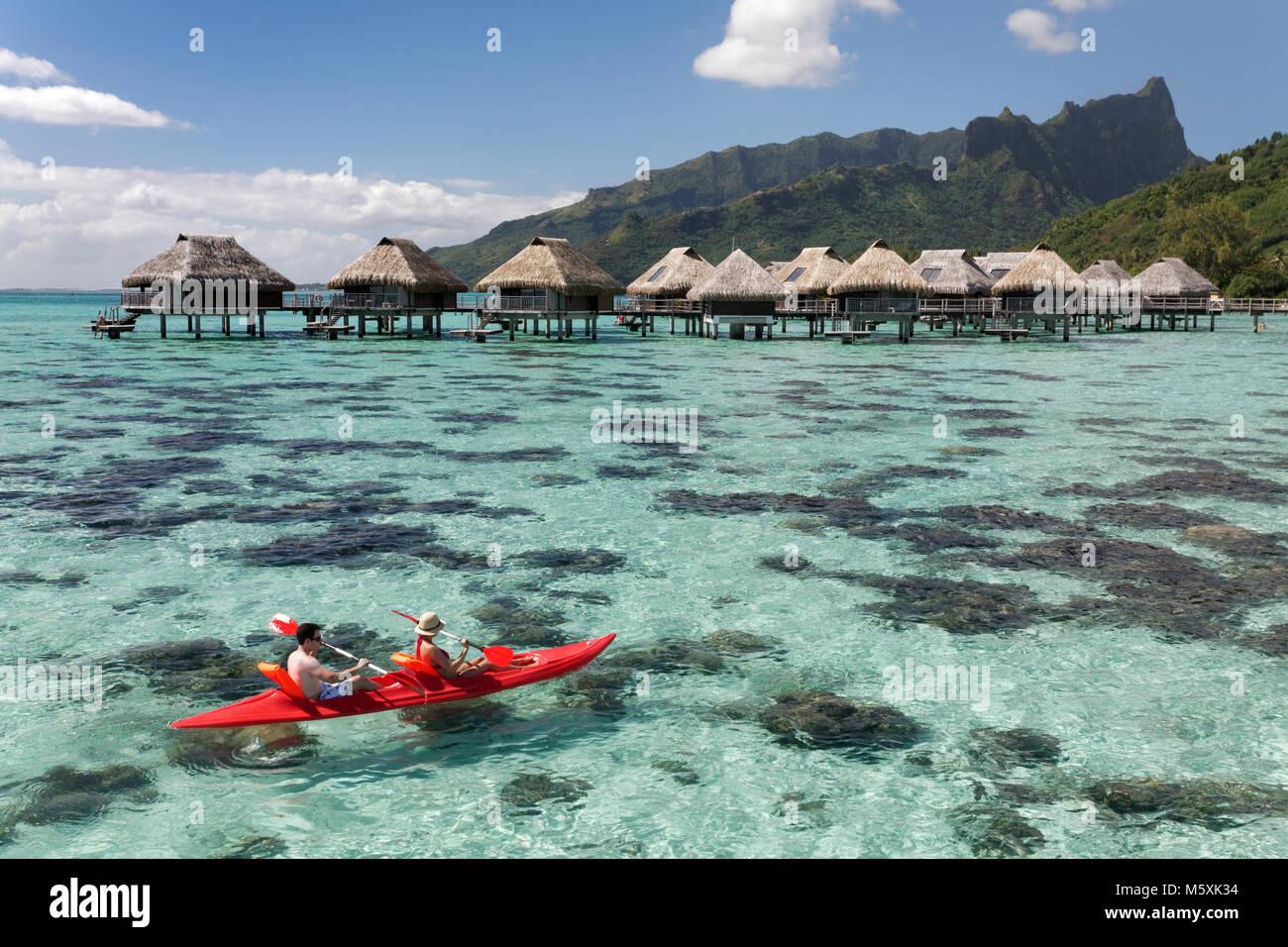 Laguna, water bungalows, paddleboat, colinas, Moorea, Océano Pacífico, Islas Sociedad, Polinesia Francesa Imagen De Stock