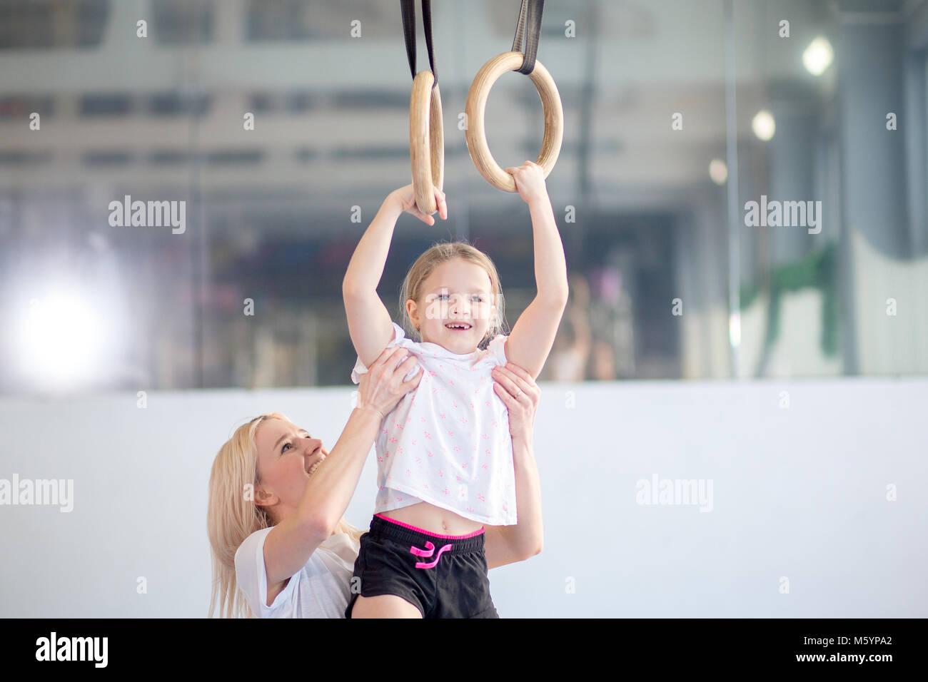 Madre ayudando a hija a jugar deportes en anillos de gimnasia Foto de stock
