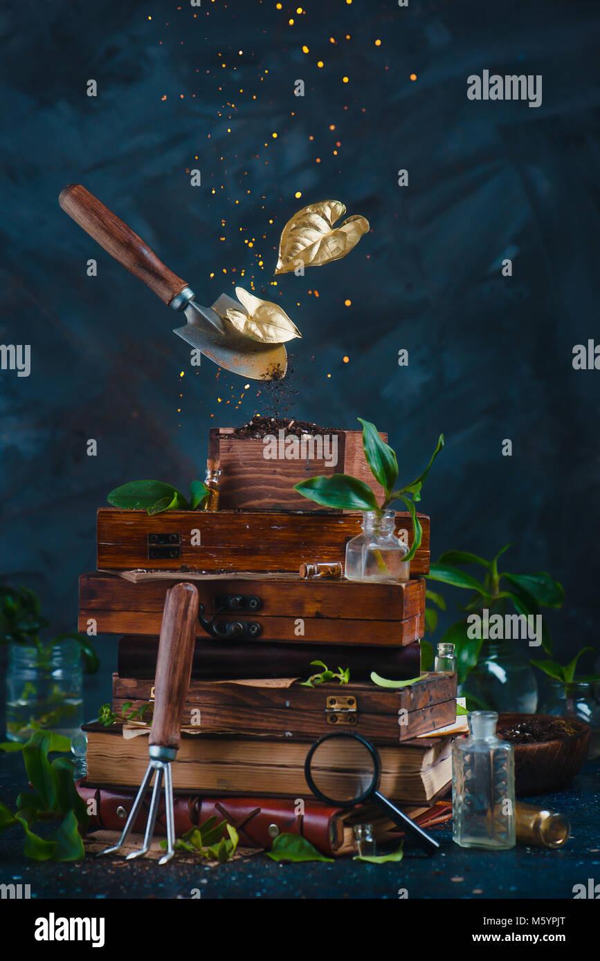 Herramientas de jardinería, una pala y un rastrillo, volando encima de la pila за vintage cajas con hojas doradas Imagen De Stock