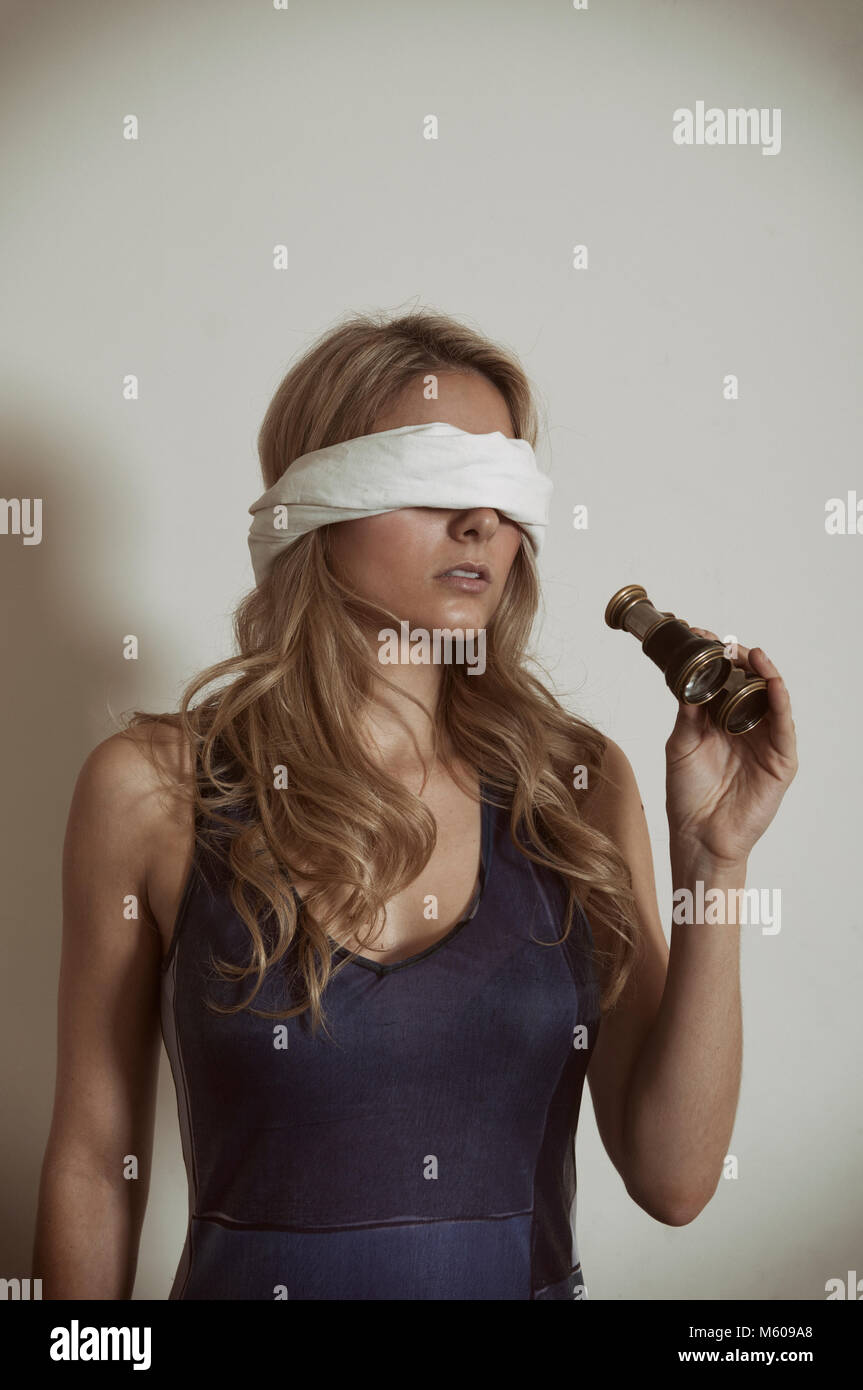 Con los ojos vendados mujer mujer sosteniendo los binoculares Imagen De Stock