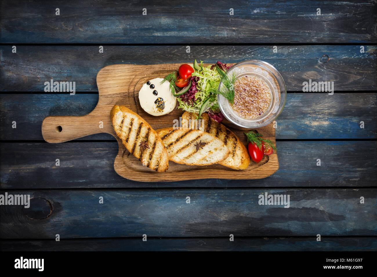 Tostadas con mantequilla y caviar sobre un fondo de madera Imagen De Stock