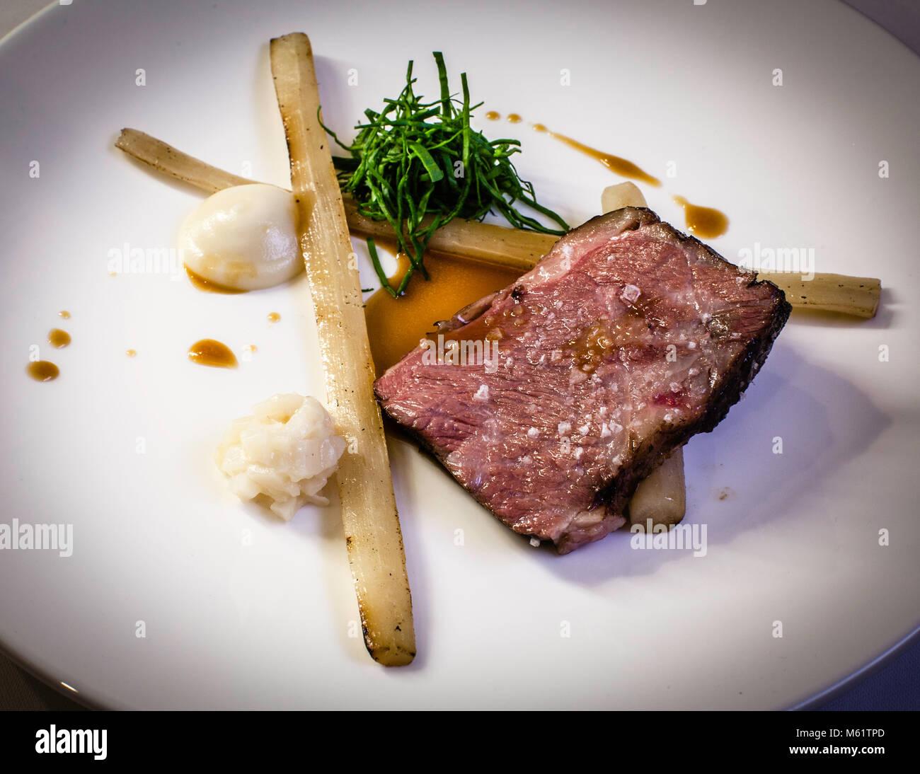 Pechuga de ternera a la parrilla con salsify y raíz de girasol por Michelin Chef Marco Müller Foto de stock
