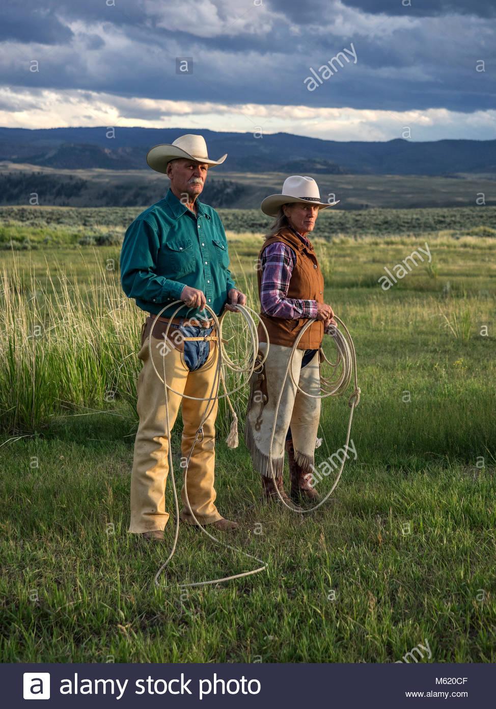 Vaquero y cowgirl celebración boleadoras sobre verdes paisajes. Imagen De Stock