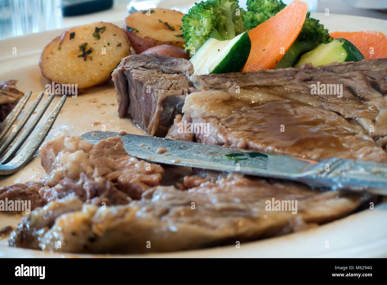La mitad comido prime rib steak en placa - EE.UU. Imagen De Stock