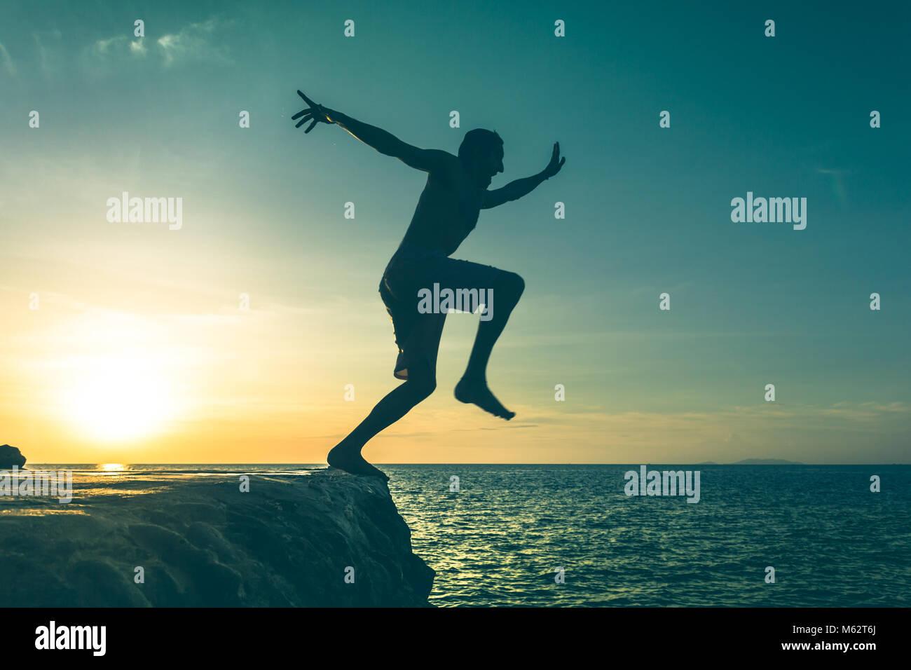 Hombre saltando sobre un acantilado en el mar a la puesta del sol en la isla de Koh Phangan, Tailandia. Efecto Vintage. Imagen De Stock