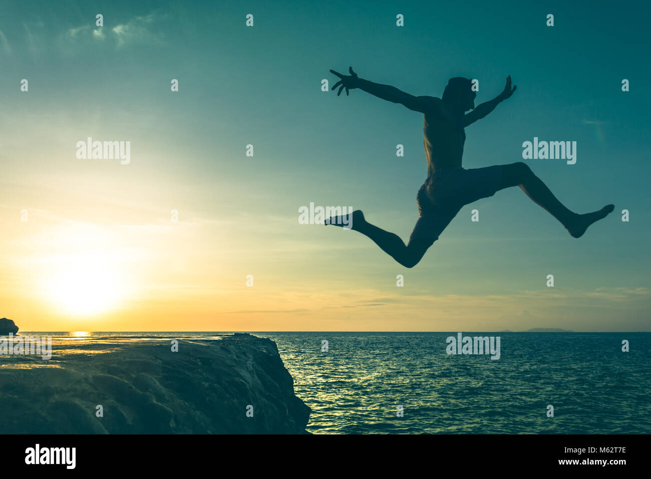 Hombre saltando sobre un acantilado en el mar a la puesta del sol en la isla de Koh Phangan, Tailandia. Efecto Vintage. Foto de stock