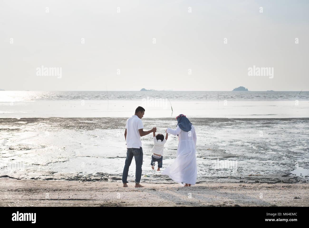 Feliz familia divirtiéndose tiempo juntos en la playa situado en Pantai Remis,Kuala Selangor, Selangor, Malasia. Imagen De Stock