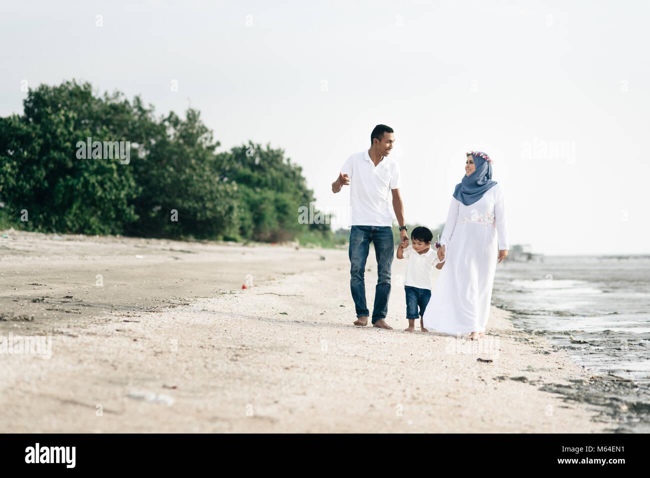 Feliz familia divirtiéndose tiempo caminando junto a la playa situado en Pantai Remis,Kuala Selangor, Selangor, Imagen De Stock