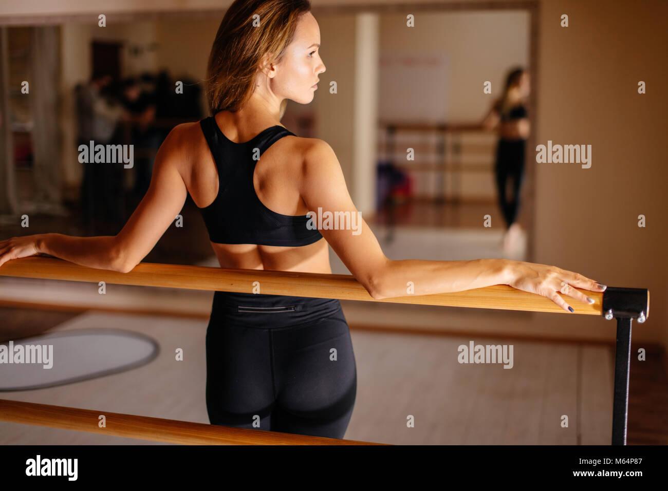 Mujer bailarina posando cerca de barre en estudio de ballet. Imagen De Stock