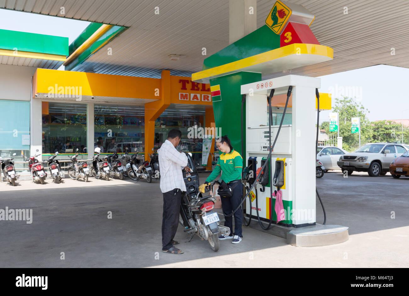 Un empleado que suministra el combustible a una motocicleta en la ciudad de Tela del petróleo - una estación Imagen De Stock