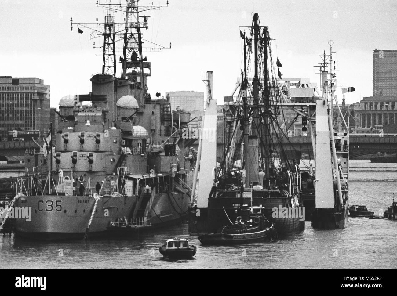 'Descubrimiento' es empujado en parcialmente sumergidas elevación pesada nave Mariner feliz junto a HMS Belfast Foto de stock
