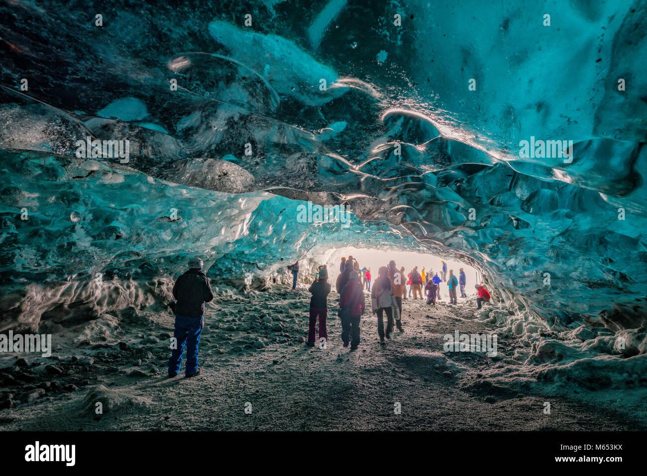 Turistas en el Crystal Cave, Glaciar Breidamerkurjokull, Islandia. Hielo azul y esmeralda ceniza es parte de Breidamerkurjokull. Imagen De Stock