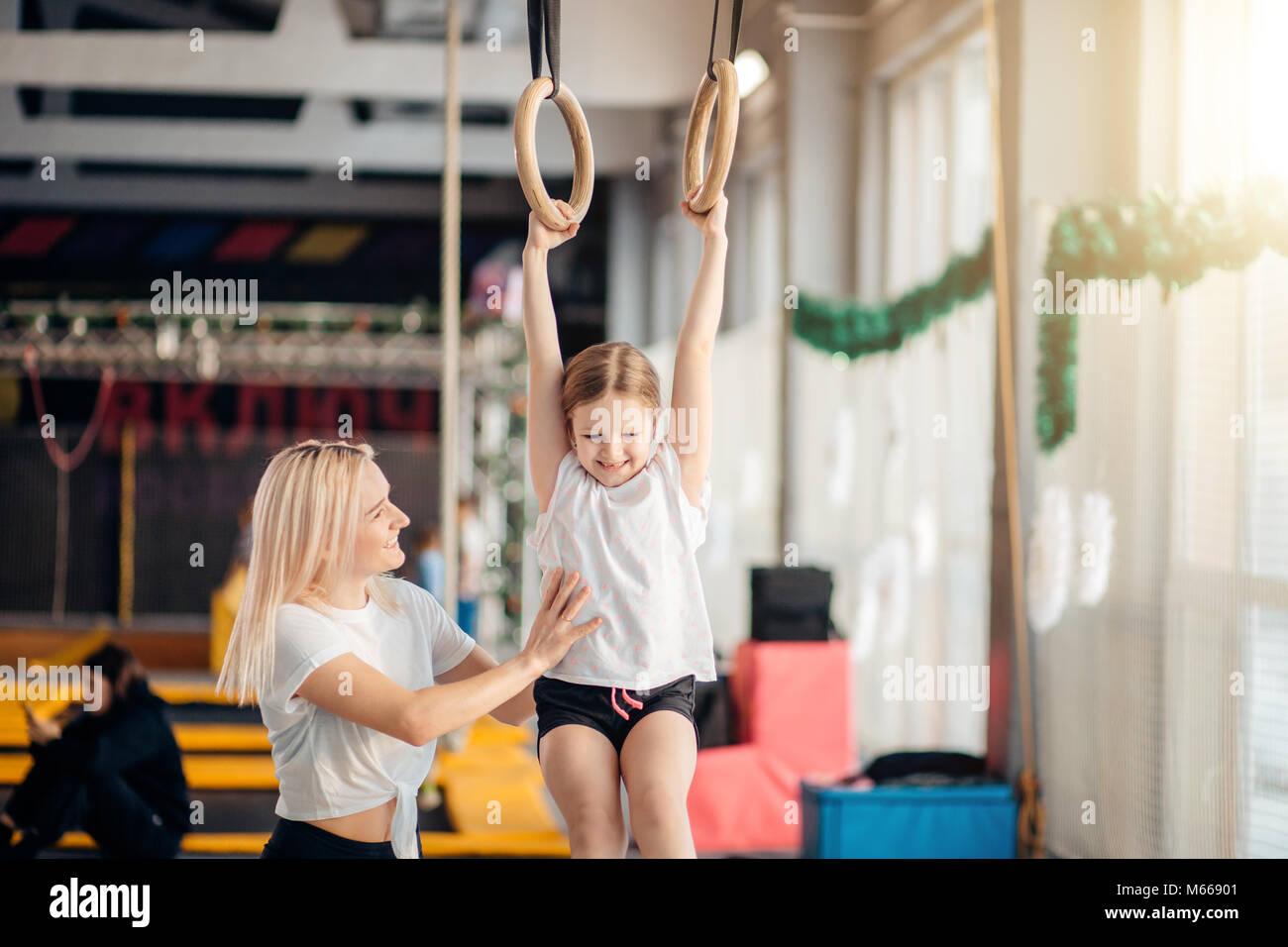 Madre ayudando a hija a jugar deportes en anillos de gimnasia Imagen De Stock