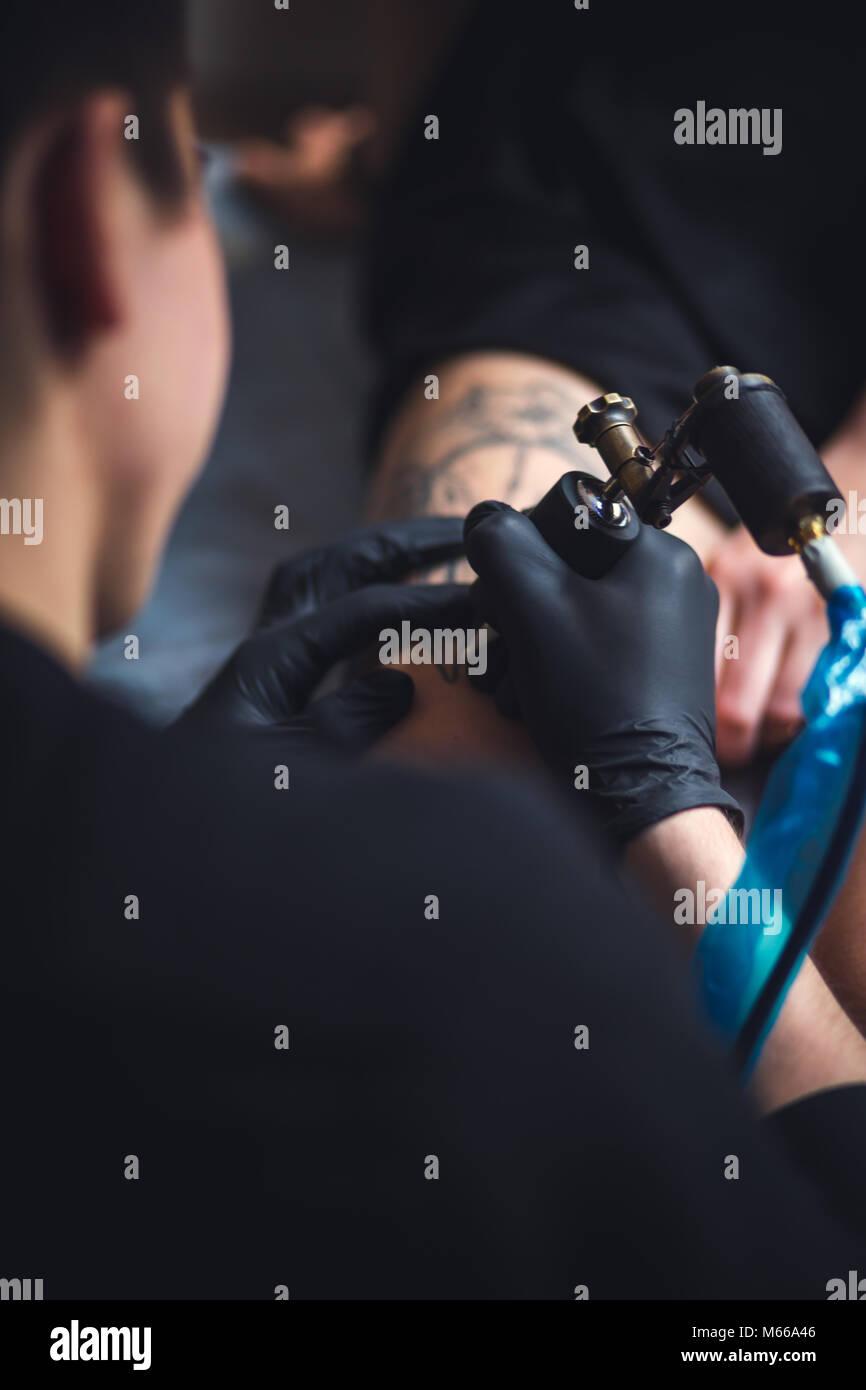 Artista masculino del tatuaje hace un tatuaje en una pierna femenina. Foto de stock