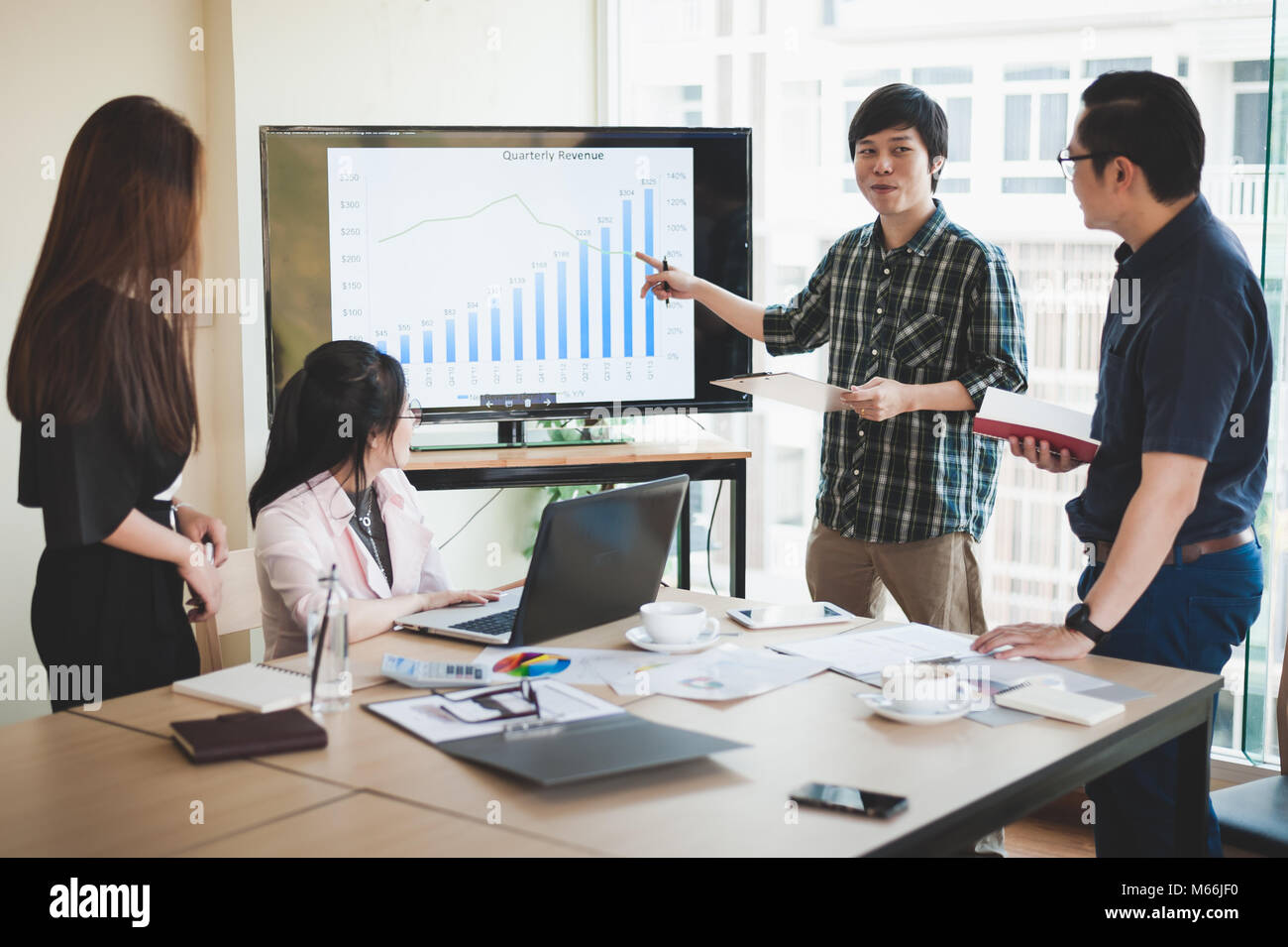 La empresaria asiática y debatir ideas con jóvenes hombre freelance en la sala de reuniones. Empresa co Imagen De Stock