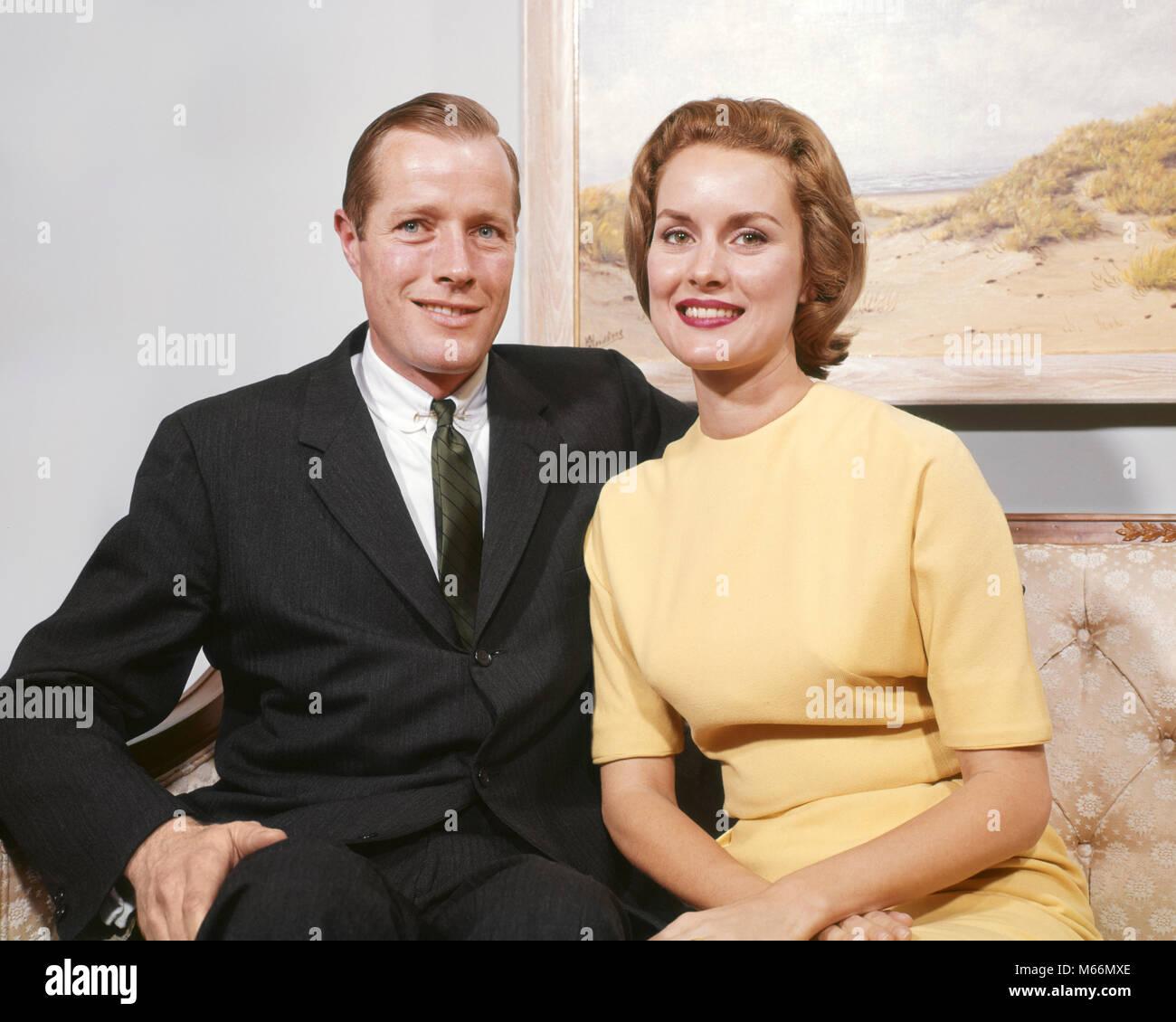 1960 atar sonriendo a vestido SENTADA en UN EN mirando feliz con traje de un cámara KP604 mujer SOFÁ pareja la la negocios a vestido amarillo hombre rpwSqrx7O