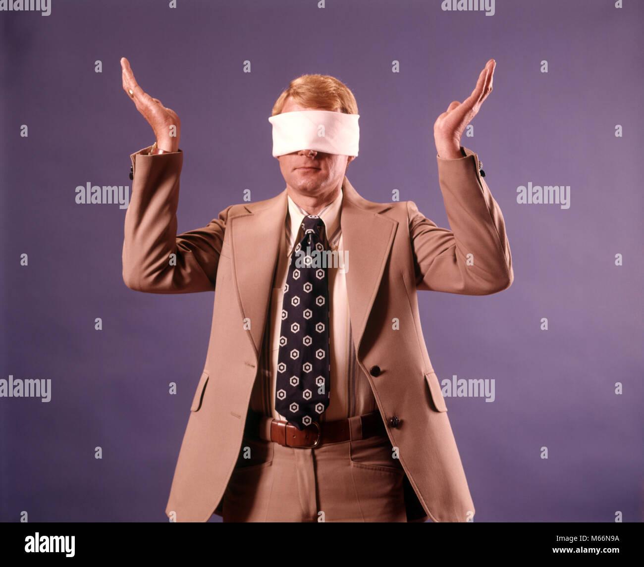 1970 Executive hombre vestido con traje de negocios vistiendo los ojos  vendados sosteniendo ambas manos en b7cc0e9f330