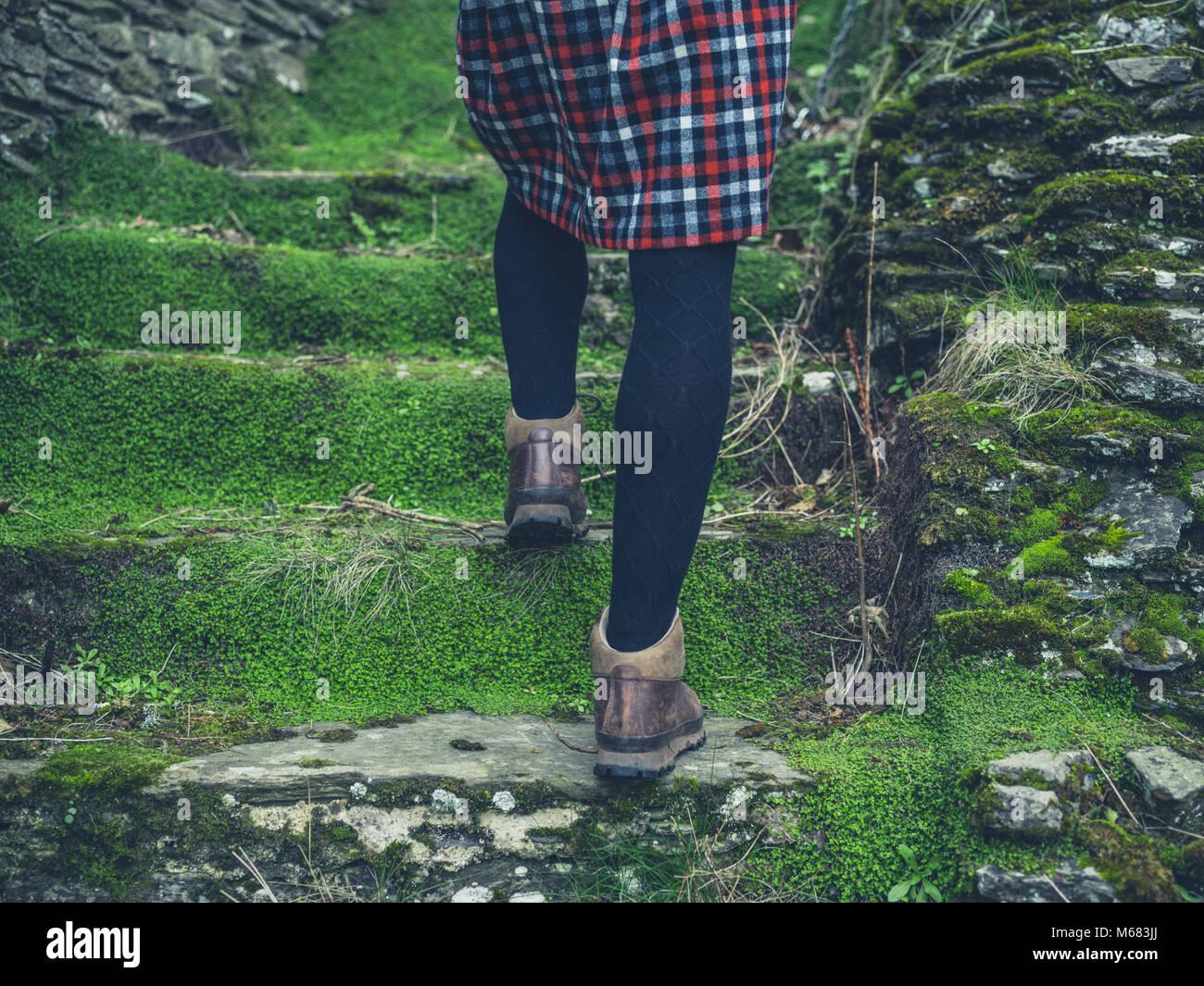 be4fd822d Una joven mujer vistiendo botas de montaña y una falda está subiendo ...