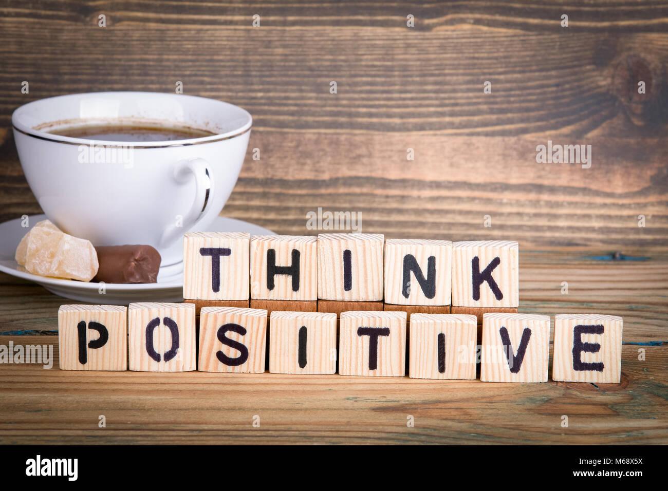 Pensar positivo. Letras de madera sobre el escritorio de la oficina, informativa y antecedentes de comunicación Imagen De Stock