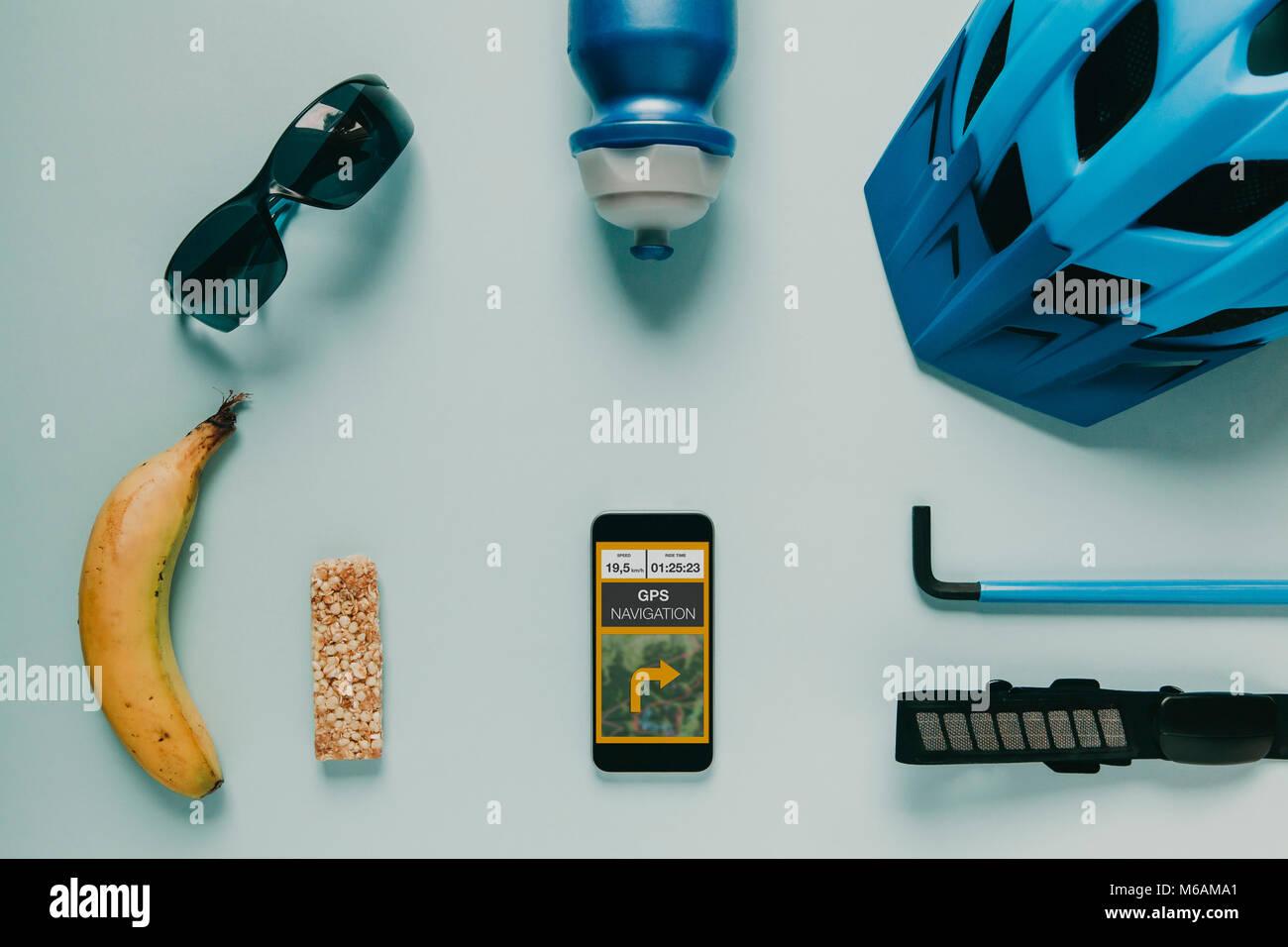 Accesorios ciclismo sobre fondo azul, y ruta GPS en la pantalla del teléfono móvil. Foto de stock