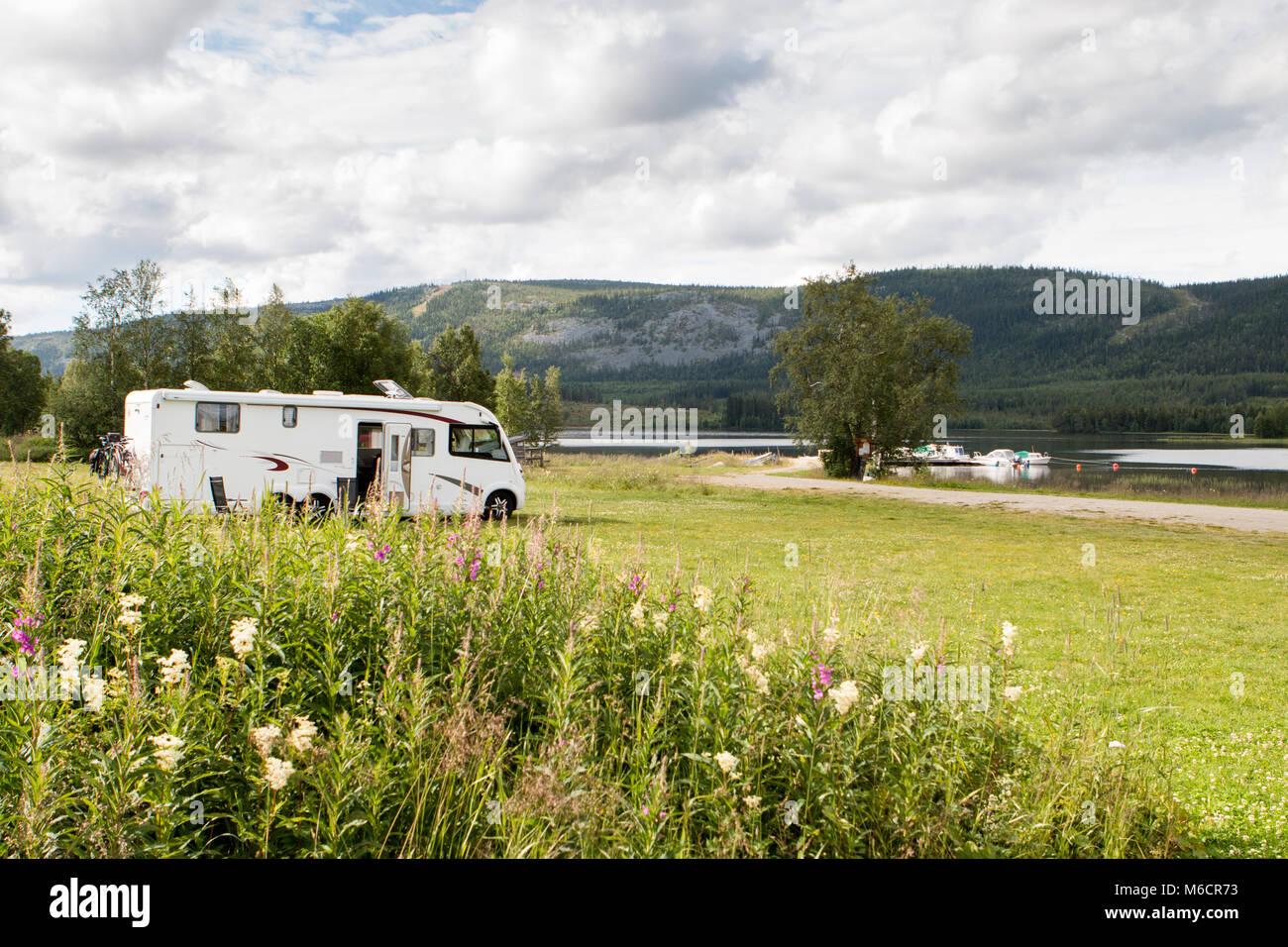 Gran casa rodante estacionada en el pasto verde cerca del lago, en Escandinavia. Imagen De Stock