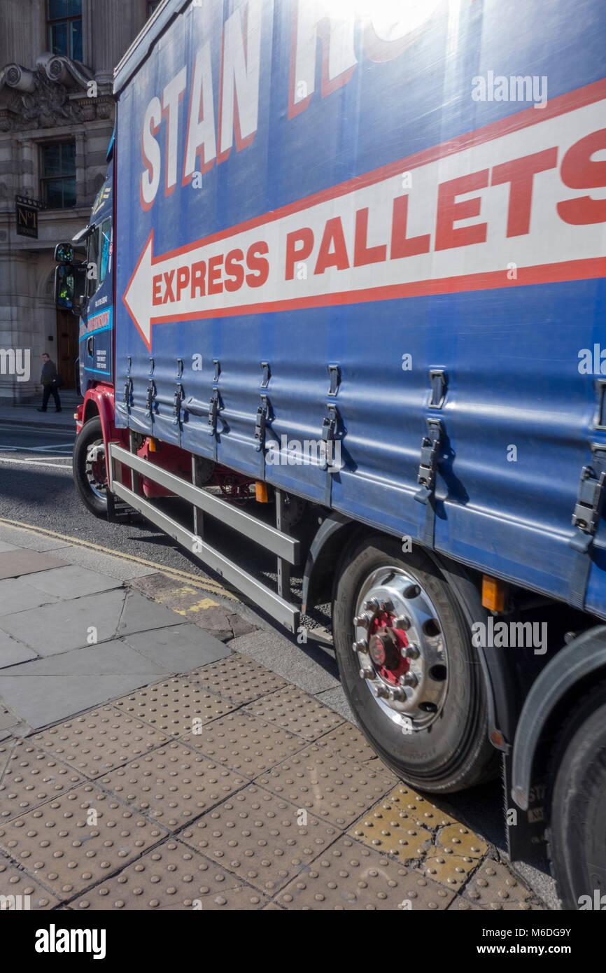 Camión pesado camión toma una curva cerrada y conducir sobre el pavimento en el cruce del Banco en Londres Foto de stock