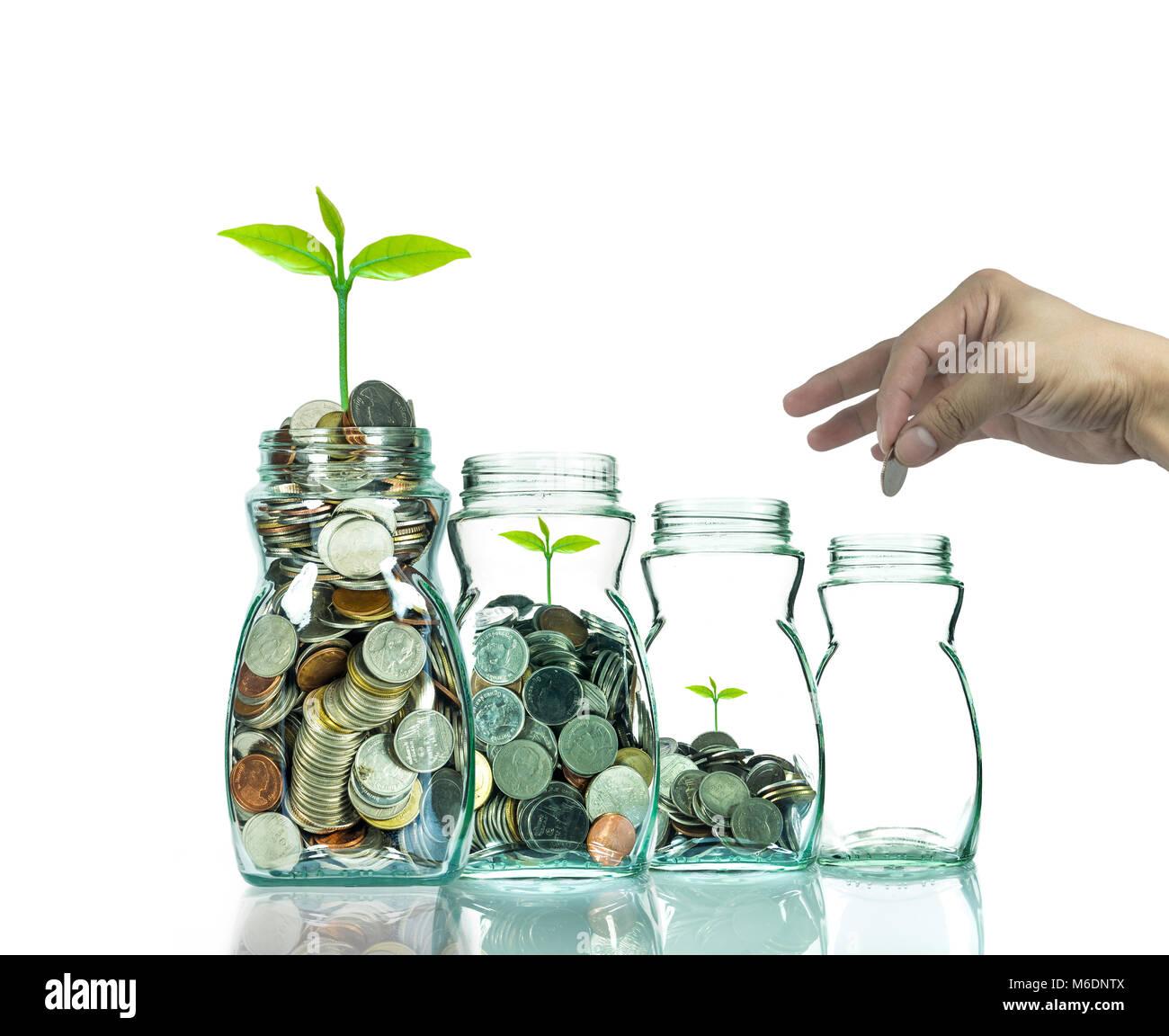 Poniendo la mano mezclar monedas y semillas en botella transparente sobre fondo blanco,el crecimiento de la inversión Imagen De Stock