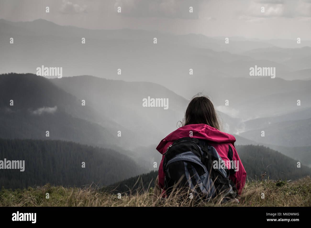 Mujer joven excursionista con mochila se sienta en el césped en la cima de la colina en los Cárpatos ucranianos Imagen De Stock