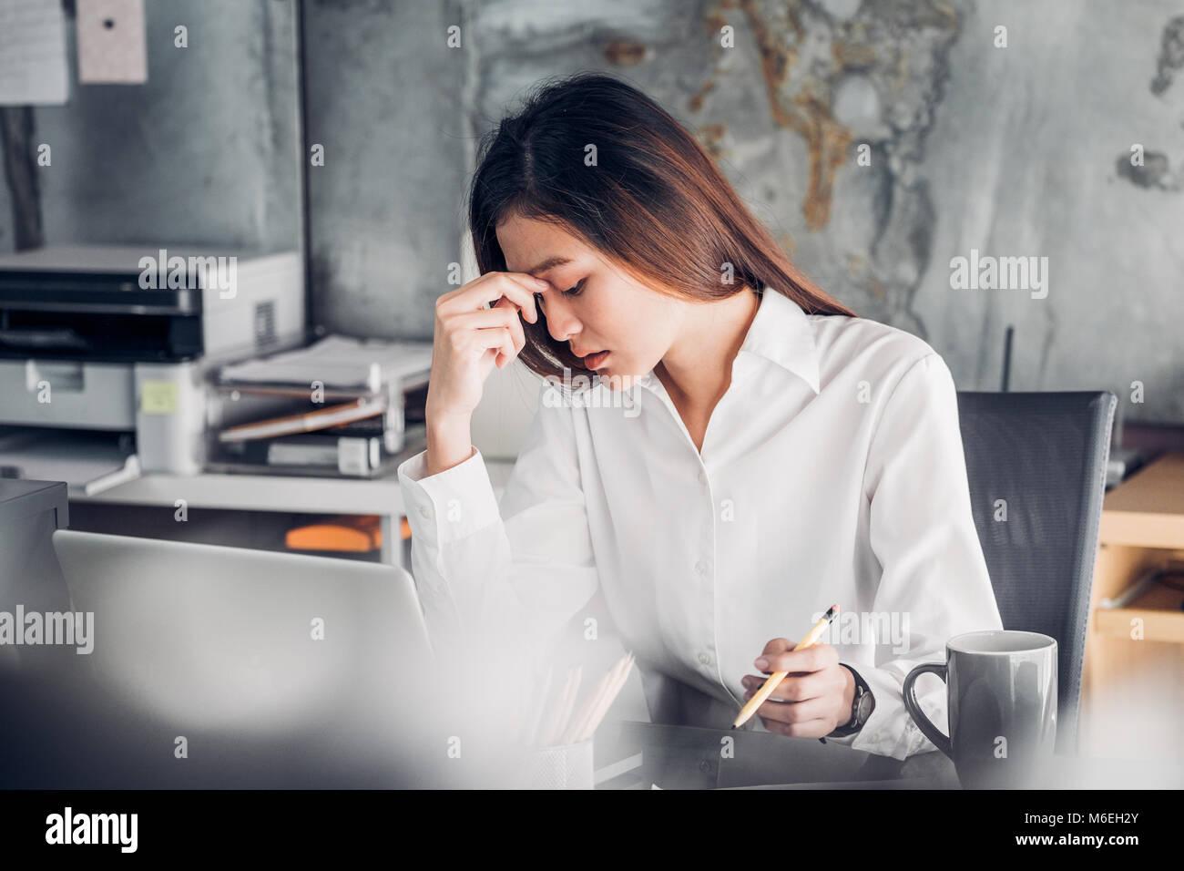 Frustrado empresaria asiática cubrir su rostro con ambas manos y sentir malestar de trabajo delante de ordenador Imagen De Stock