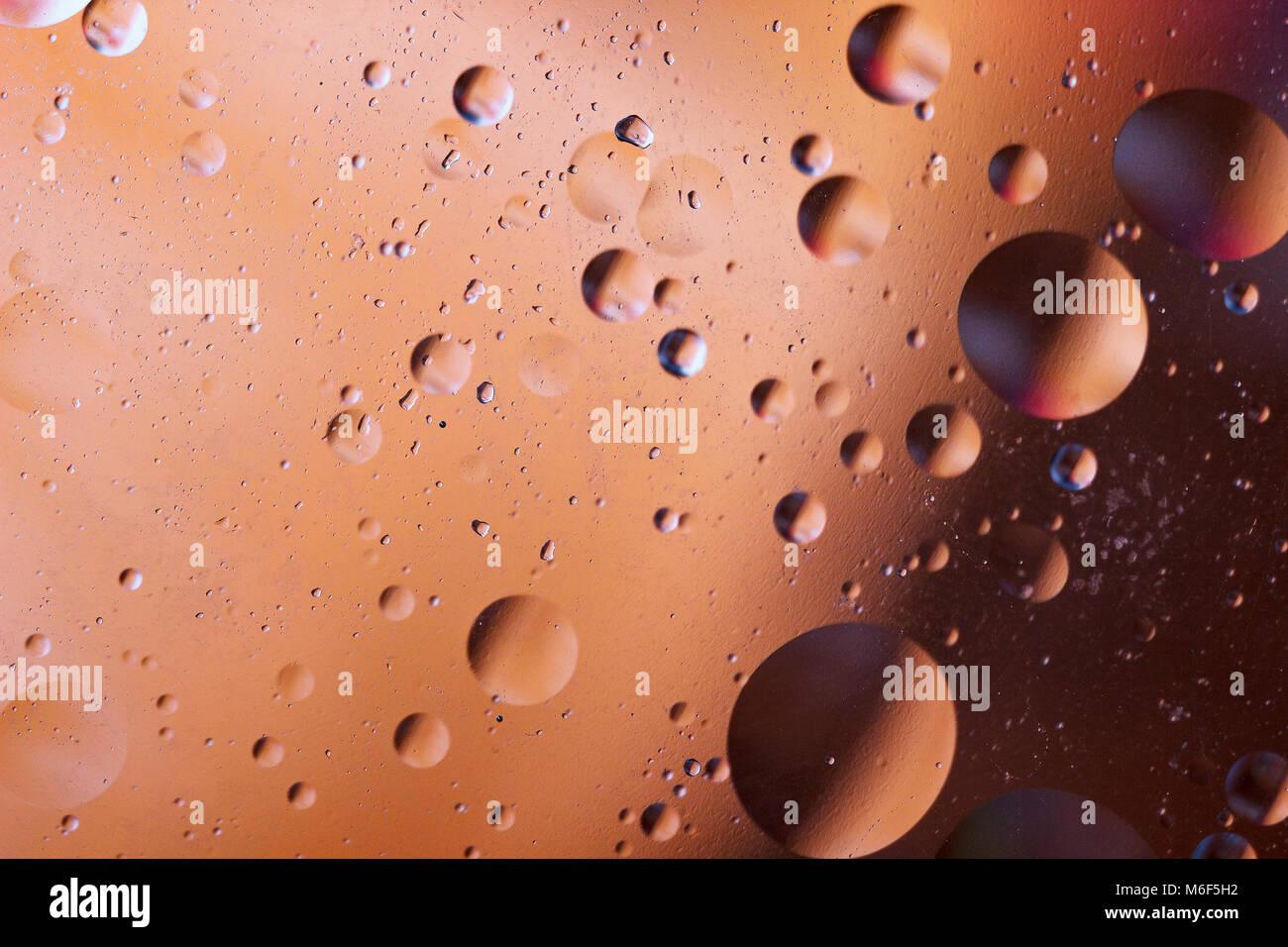 Burbujas de aceite en un medio acuoso en la frontera, con una superficie de cristal. Protector de pantalla de abstractos. Foto de stock