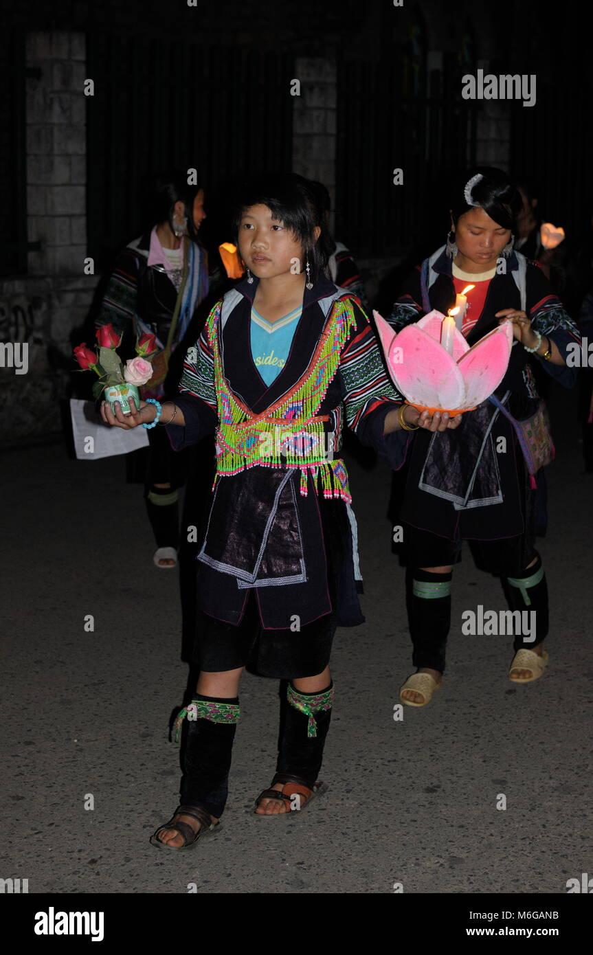 Feliz joven Hmong y solemnes muchachas vestidas en trajes tradicionales Sosteniendo velas y flores celebrando la Imagen De Stock