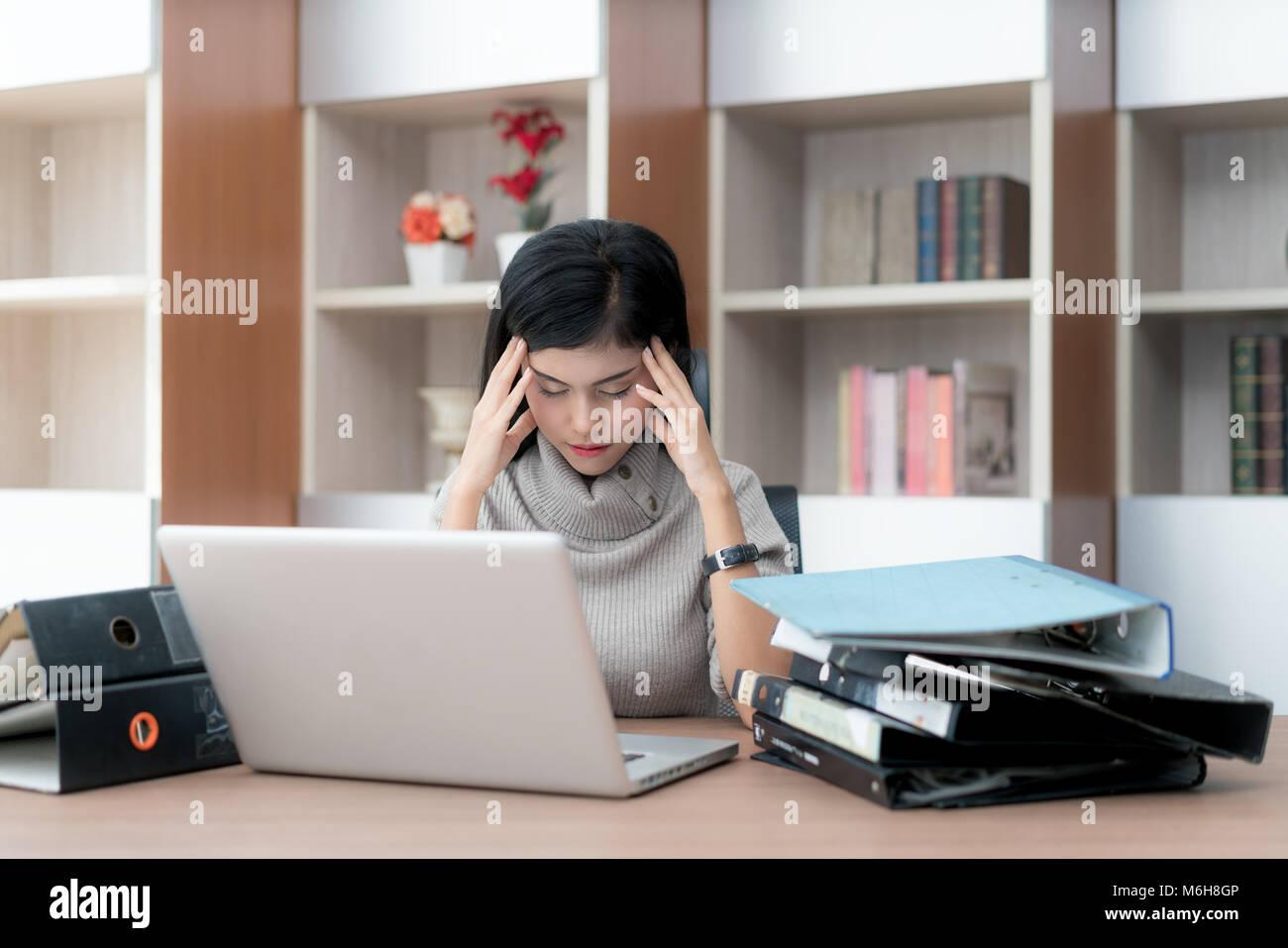 Retrato de cansado joven mujer de negocios asiáticos sensación de estrés de un montón de trabajo. Imagen De Stock
