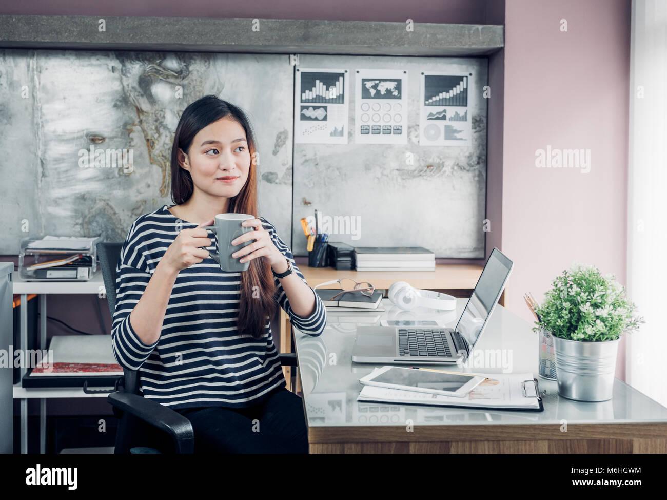 La empresaria asiática tomar un café después de trabajar con cara sonriente, feliz de la vida de Imagen De Stock