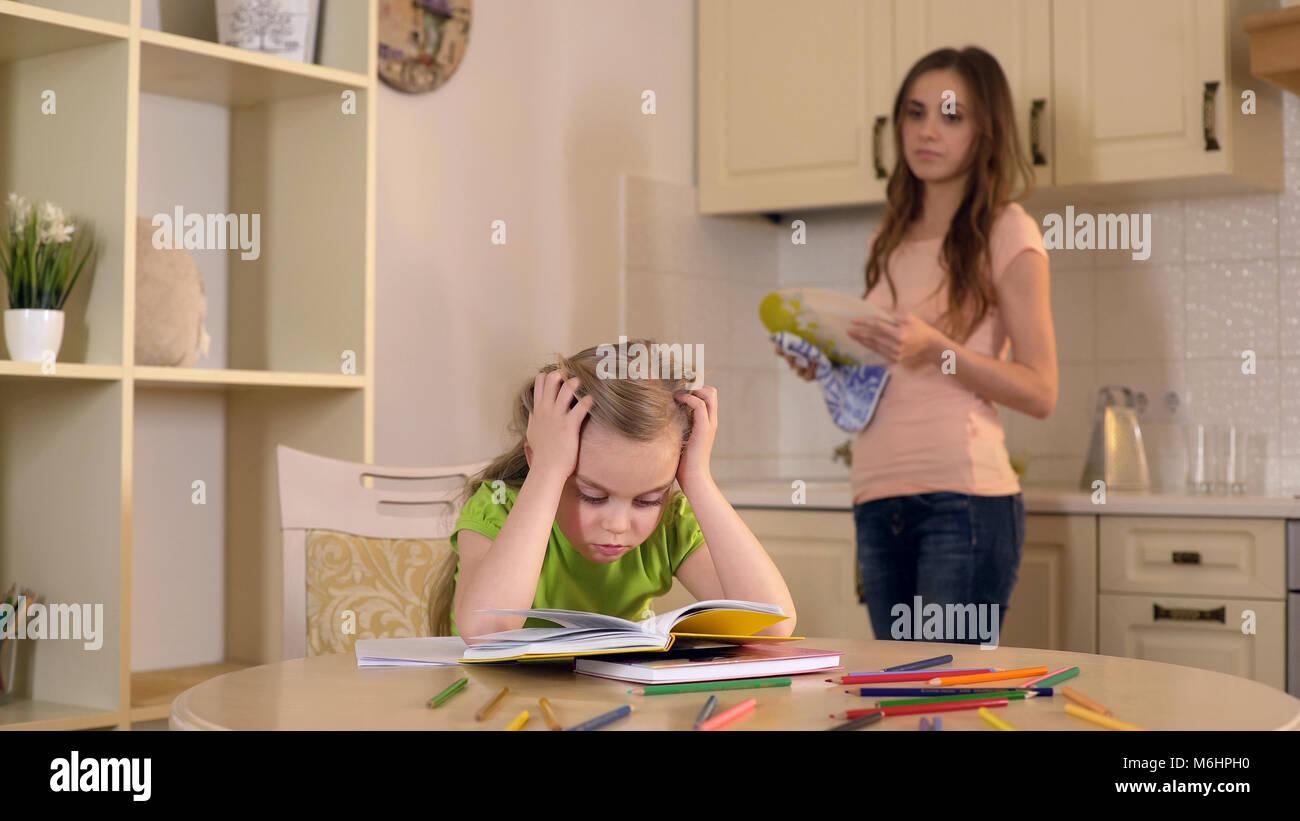 Mamá lavando platos viendo como su hija hace sus deberes con dificultad Imagen De Stock