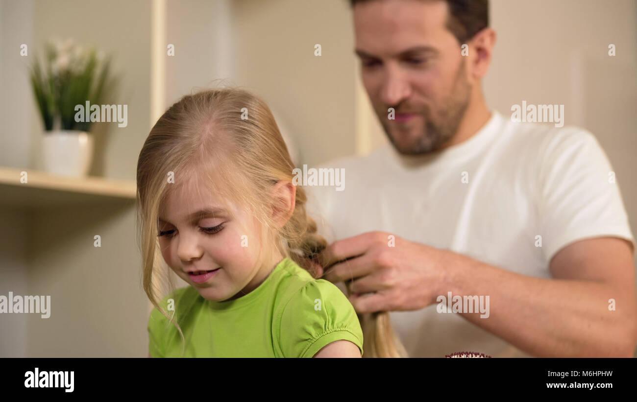 Padre soltero feliz trenzar el cabello de su hija, teniendo cuidado de la querida niña Imagen De Stock