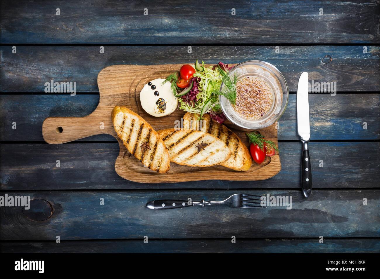 Tostadas con mantequilla y caviar servidos con cubertería sobre un fondo de madera Imagen De Stock