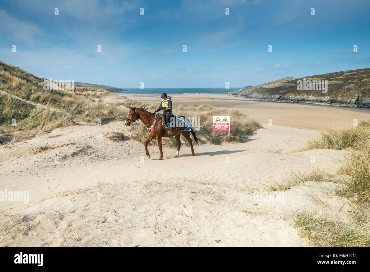 Un jinete sobre las dunas de arena en la playa Crantock en Newquay, Cornwall. Imagen De Stock
