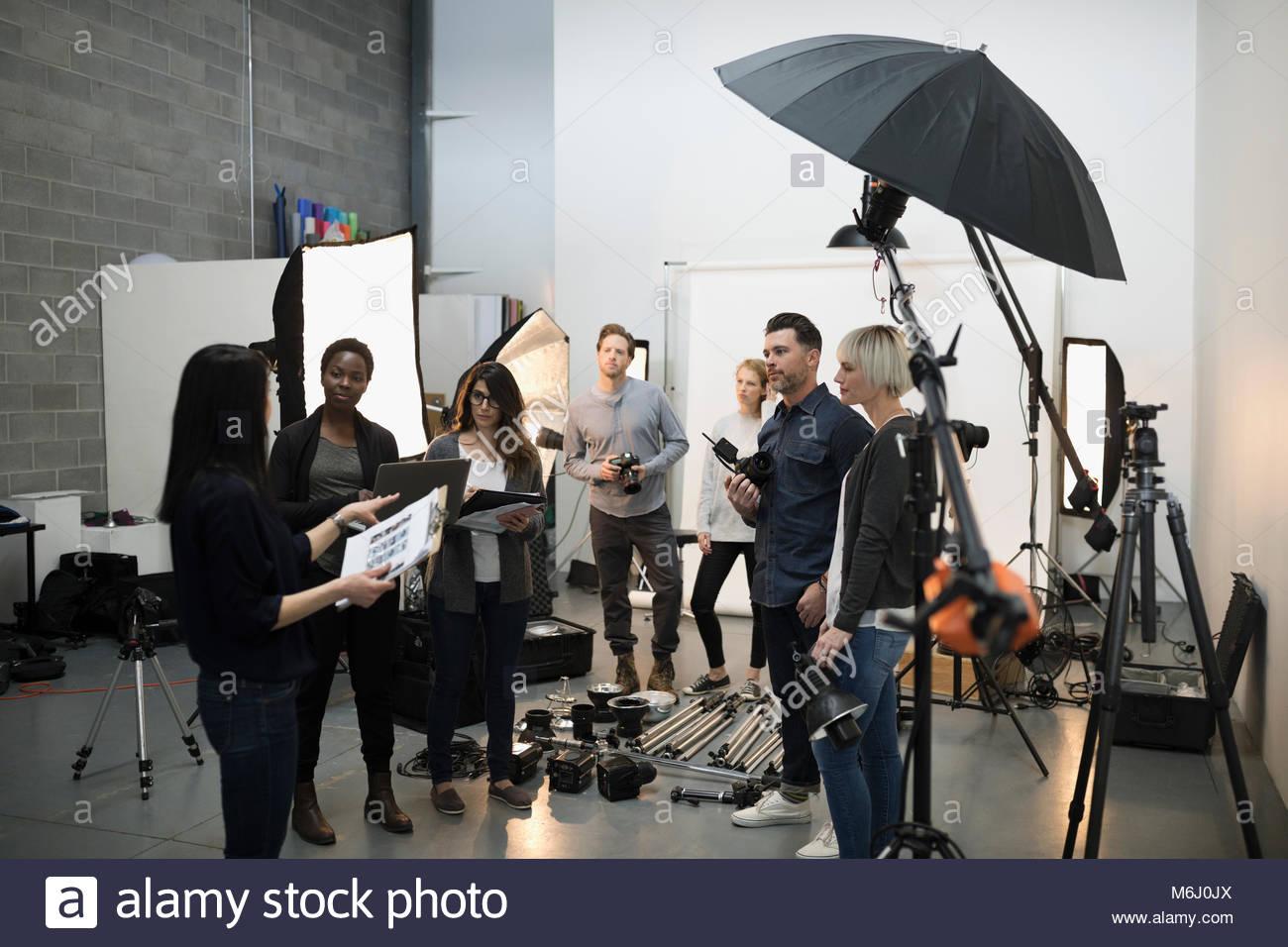 Fotógrafos y reunión de equipo de producción, preparación para fotos en estudio Imagen De Stock