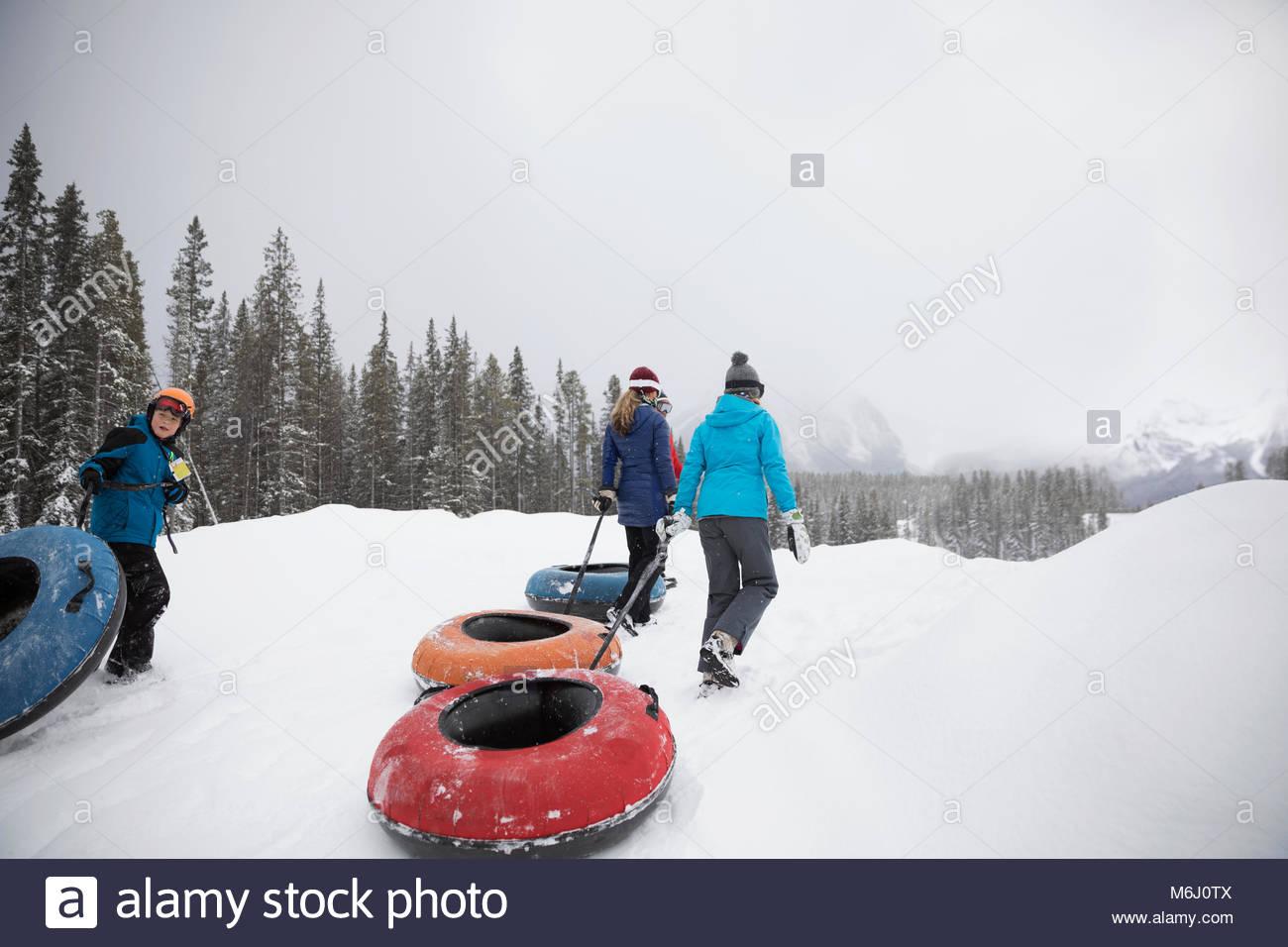 Familia tirando de los tubos interiores en la nieve en el metro park Imagen De Stock