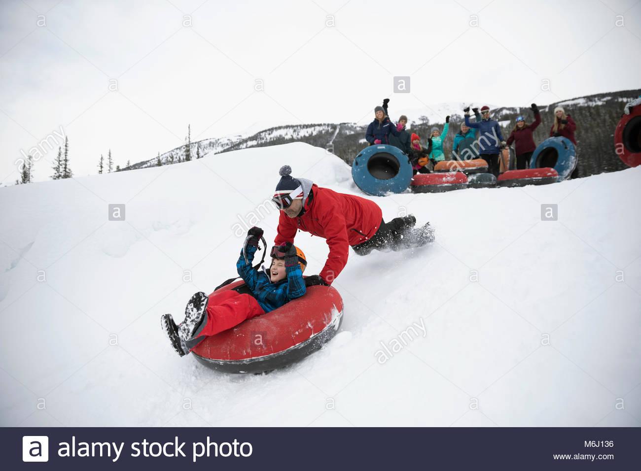 Familia hijo de padre vítores empujando el tubo interior en la nieve en el metro park Imagen De Stock