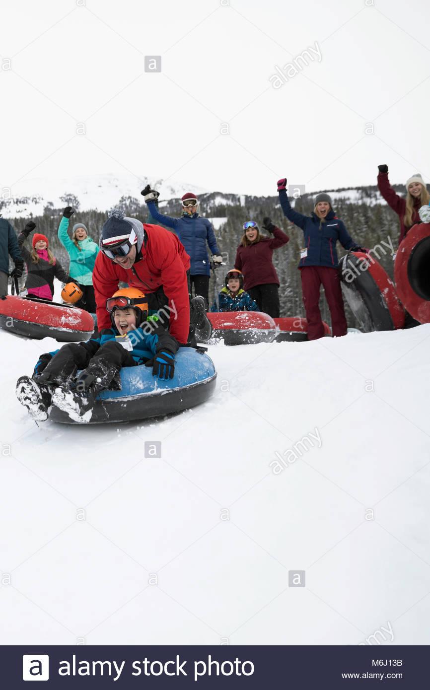 Familia hijo de padre vítores empujando el tubo interior en la nieve Imagen De Stock