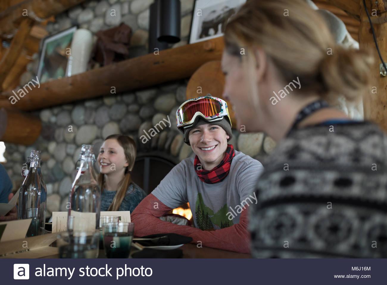 Esquiador sonriente hijo con familia en ski resort lodge restaurant Imagen De Stock