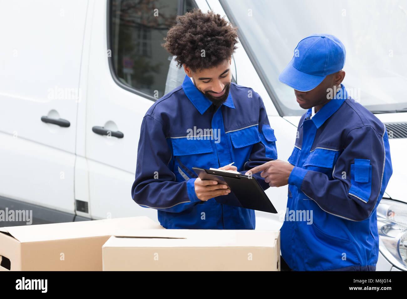 Delivery Man escrito en el Portapapeles encima de las cajas de cartón junto al camión. Imagen De Stock