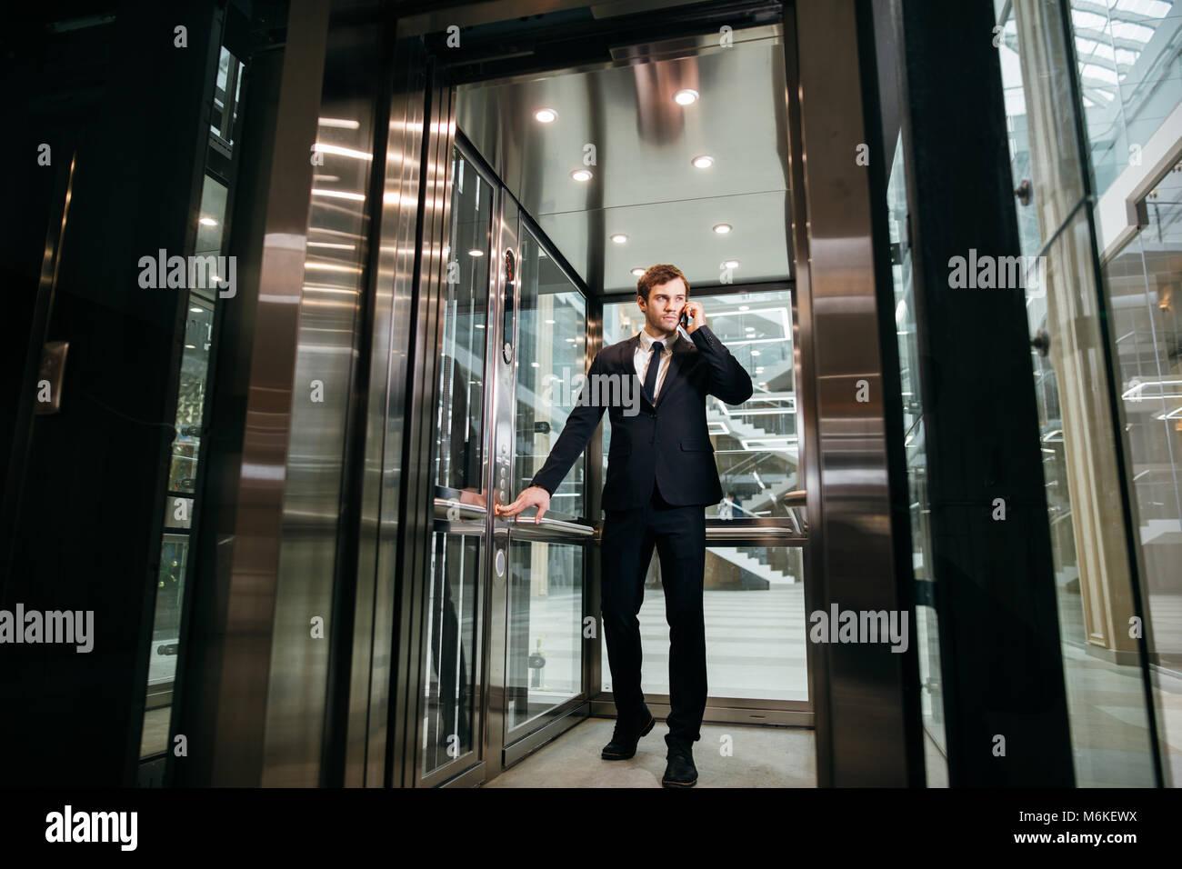Hombre de negocios caminar mientras habla por teléfono móvil en su camino al trabajo Imagen De Stock