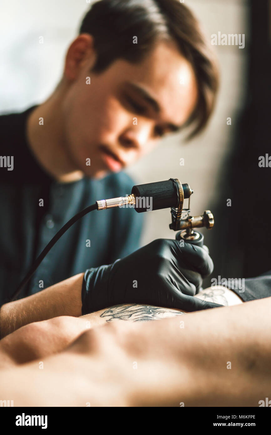 Artista masculino del tatuaje hace un tatuaje en una pierna femenina. Imagen De Stock
