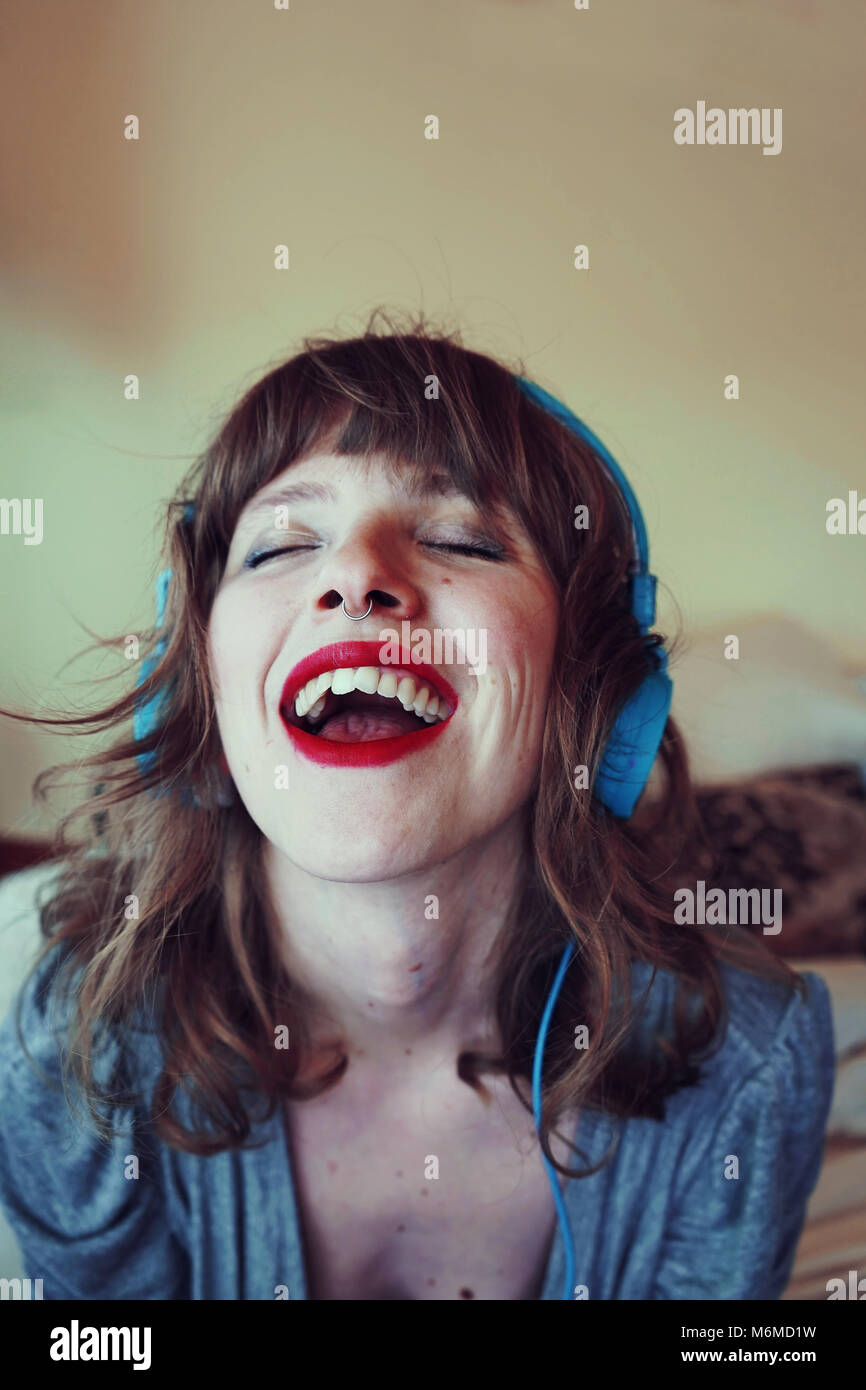 Mujer joven en casa escuchando música Foto de stock