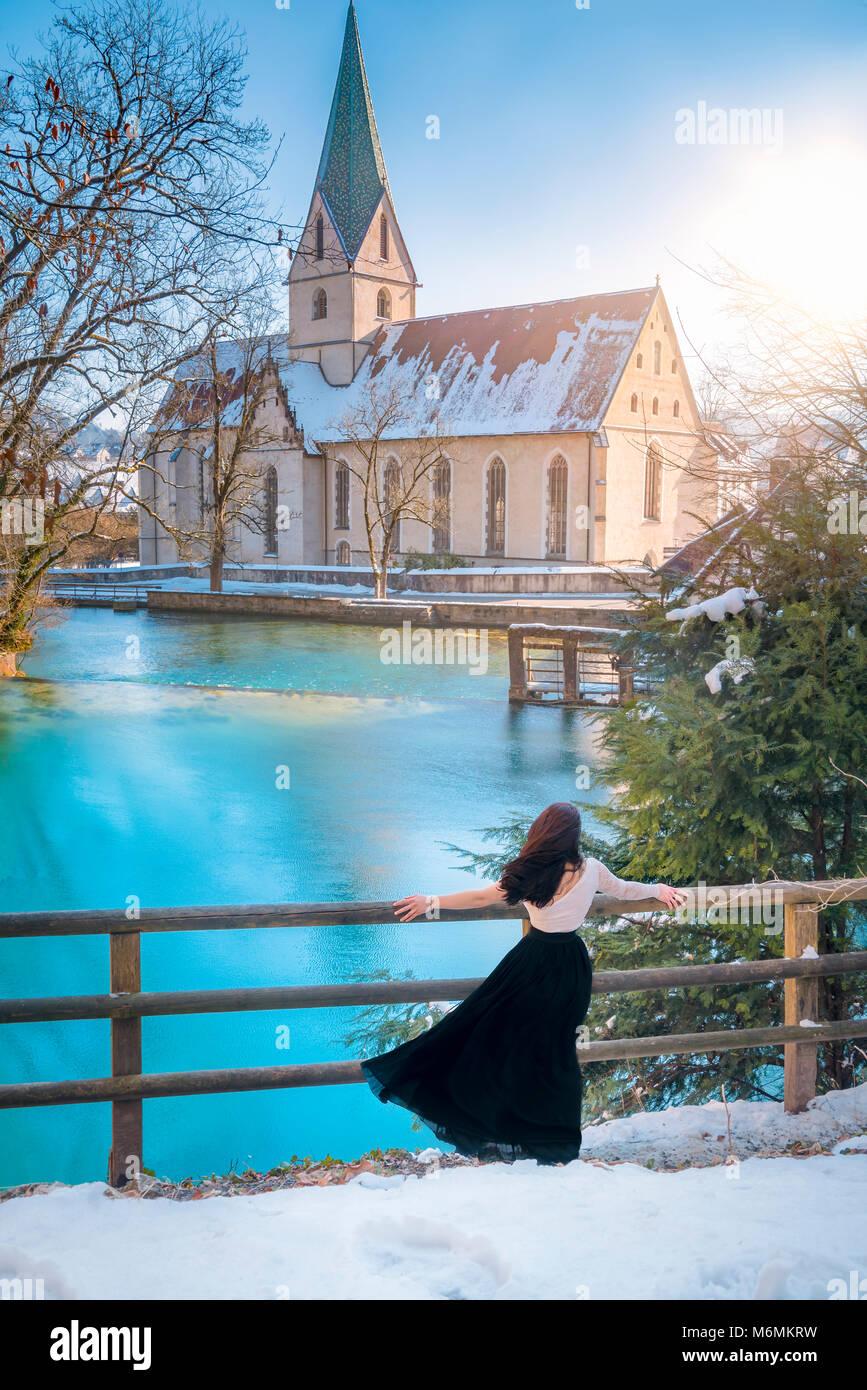 Vista trasera de un atractivo joven, vestida elegantemente, admirando el azul del agua de la Blautopf primavera, en un día soleado, en Blaubeuren, Alemania. Foto de stock