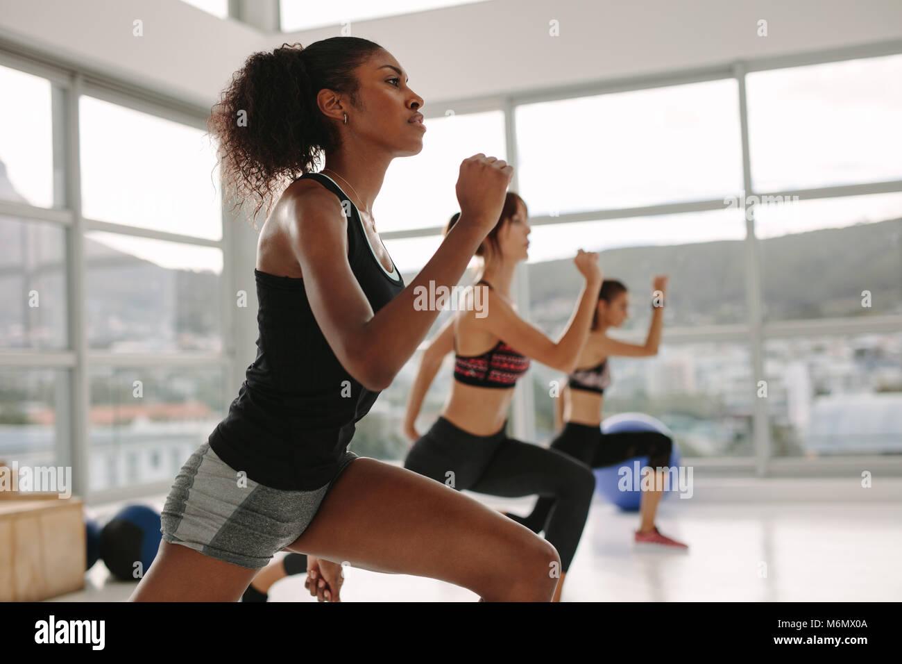 Mujer joven en ropa deportiva haciendo ejercicio durante el intenso entrenamiento de circuito en la clase de gimnasia. Imagen De Stock