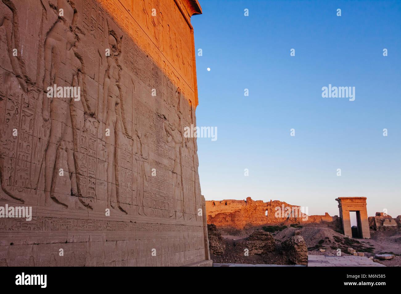 Bajo-relieves en el exterior del templo de Hathor con uno de los gateways del compuesto en el fondo al atardecer. Imagen De Stock